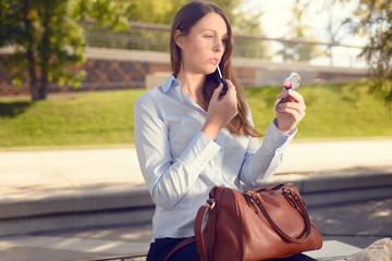 Attraktive Geschäftsfrau trägt Lippenstift auf