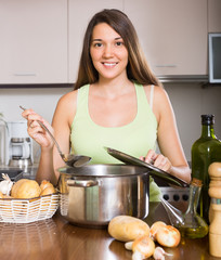 Woman with ladle cooking soup