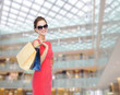smiling elegant woman in dress with shopping bags