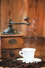 Cup of black coffee in the background grinder on a wooden rustic