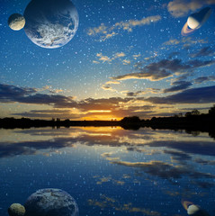 Sunset over the lake on a sky background with planets
