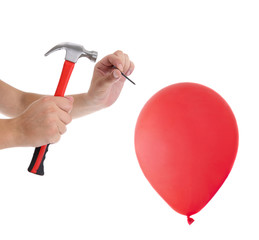 Man hitting a nail into a red balloon on the white background