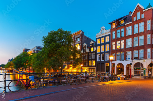 canvas print picture Night city view of Amsterdam canal and bridge
