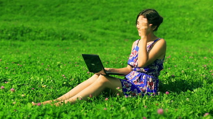 Happy woman sitting on the meadow and chatting on laptop