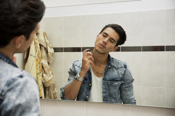 Handsome young man in his home bathroom, spraying cologne or per