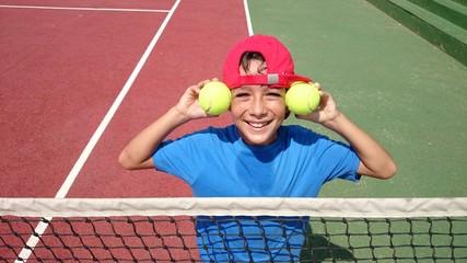 Niño con pelotas de tenis