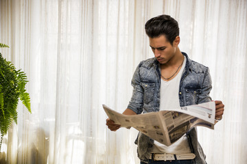 Handsome young man at home reading newspaper, standing