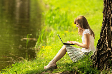 Young woman using Laptop on nature