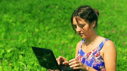 Happy woman sitting on the grass and typing on laptop