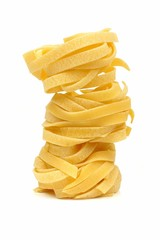 Stack of tagliatelle pasta nests over a white background
