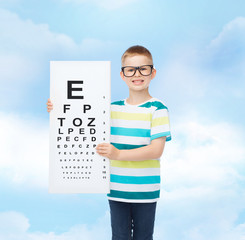 smiling boy in eyeglasses with white blank board