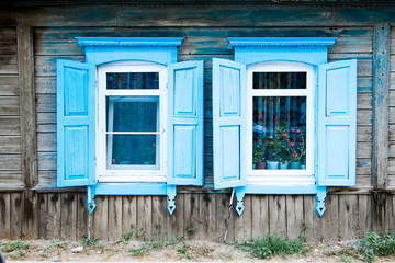 Two aged window of a old wooden house in Russia