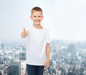 smiling boy in white t-shirt showing thumbs up