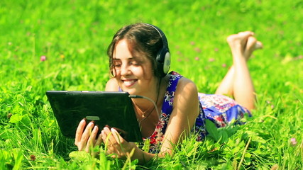 Happy woman watching something on tablet and smiling