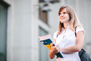 Young female student standing near university holding books