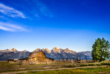 Landscape view of Grand Teton mountain range and abandoned barn