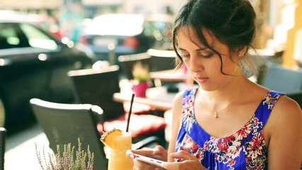 Pretty girl sitting in the street cafe and texting on smartphone