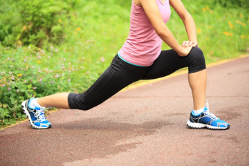woman runner stretching legs on forest trail