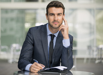 Imperturbable businessman holding a pen staring at you