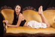 woman laying down on gold couch