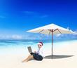Businessman Wearing a Santa Hat on a Beach