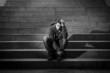 Leinwandbild Motiv Young man jobless in depression sitting homeless on street