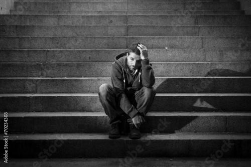 Leinwanddruck Bild Young man jobless in depression sitting homeless on street