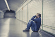 Leinwanddruck Bild - Young sad man sick and depressed sitting on ground street tunnel