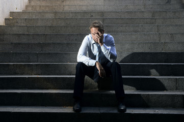 businessman crying depressed sitting on concrete stairs