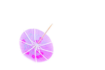 Pink cocktail umbrella on white background