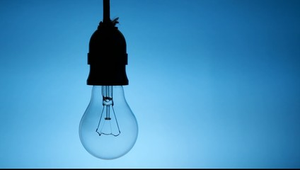 Close up on lightbulb flickers on blue background