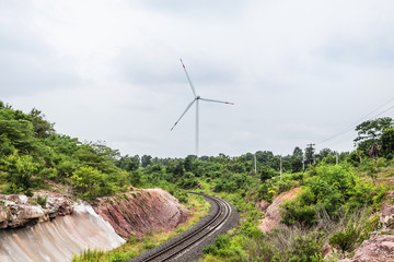 wind turbines generating electricity behind railroad tracks