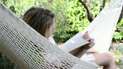 cheerful young woman reading in a hammock