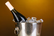 Bottle of wine in ice bucket on darck yellow background