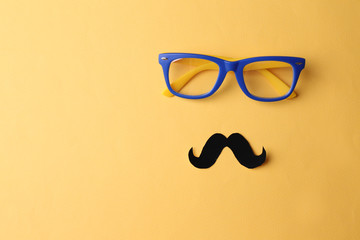 Glasses and mustache forming man face on yellow background