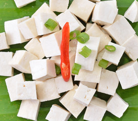 Raw tofu cut in dices on banana leaves