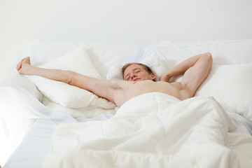 Single man waking up in bed