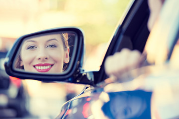 Woman driver looking in car side view mirror smiling