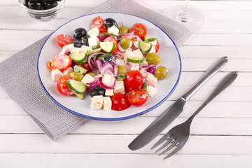Greek salad served in plate on napkin on wooden background