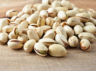 Pistachio nuts, close up on wooden table