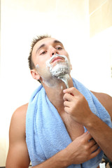 Young man shaving his beard in bathroom