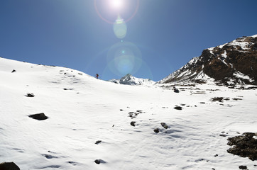 Alpinisht climbing mountains through deep snow under bright sun