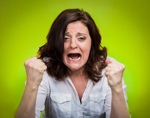 portrait young angry woman screaming on green background