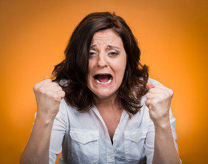 portrait young angry woman screaming on orange background