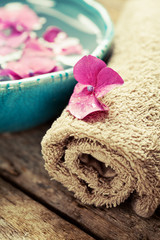 Bottle of essential oil, bowl with flowers and towel