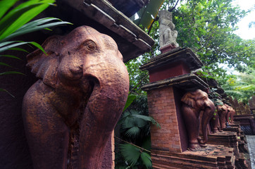 Stone elephant statues of bronze color in a sacred park