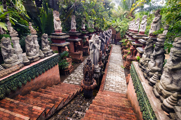 Stairs in a sacred park with numerous religious statues of gods