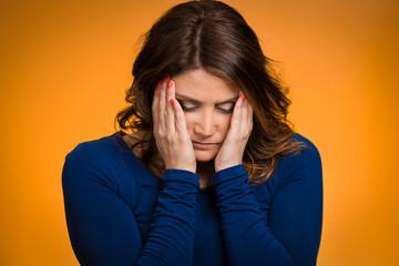 Headshot depressed, gloomy woman on orange background