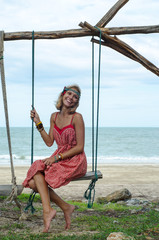 Young Hippie Woman on a Swing Enjoying Summer Day at the Seaside