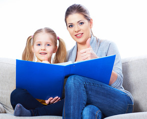 Mother reading book with daughter at home.